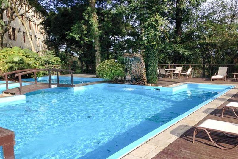Cascata piscina detalhes espreguiçadeiras e sombra