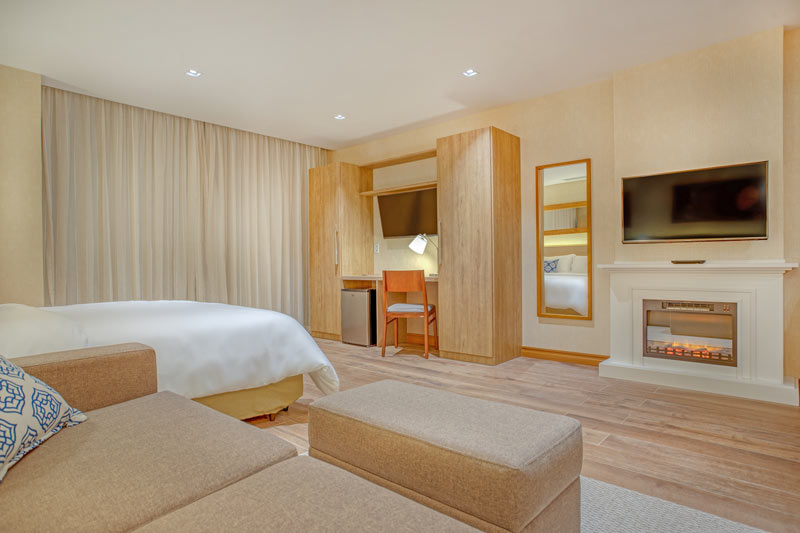 frente cama com lareira e televisão