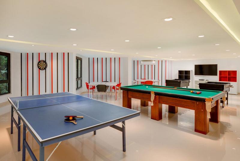 Sala de jogos com ping-pong e sinuca ao fundo